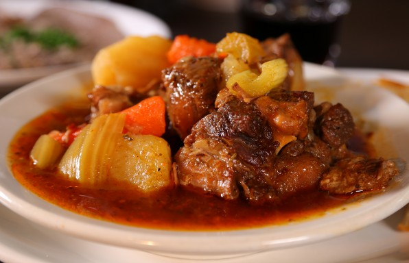 Bowl of oxtail stew with a side of bread from Pyrenees Café in Bakersfield, CA as seen on Food Network's Diners, Drive-Ins and Dives episode DV2209.
